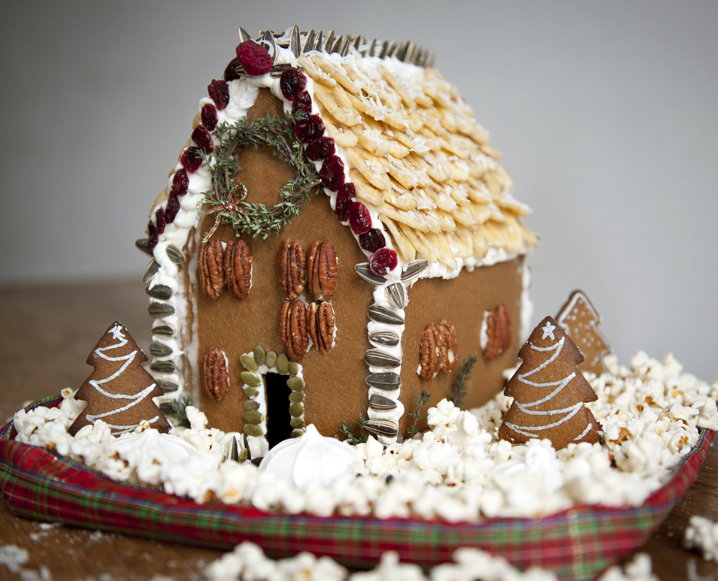 pecan gingerbread house with rosemary tree wreath decoration.